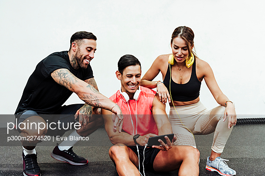 Smiling male and female athletes using mobile phone in gym - p300m2274520 by Eva Blanco