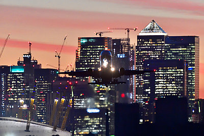 Airliner flying over London skyscrapers - p1048m2024241 by Mark Wagner