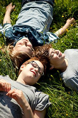 Drei Jungen liegen auf einer Wiese in der Sonne - p1195m1138105 von Kathrin Brunnhofer