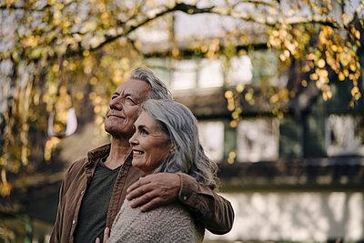 Affectionate senior couple in garden of their home in autumn - p300m2156099 von Gustafsson