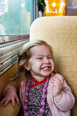 Caucasian girl grinning near window on train - p555m1491652 by Adam Hester