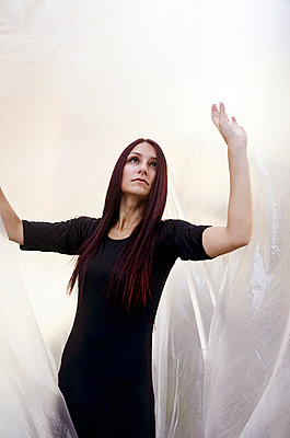 Portrait of young woman standing under plastic sheet - p577m2038721 by Mihaela Ninic