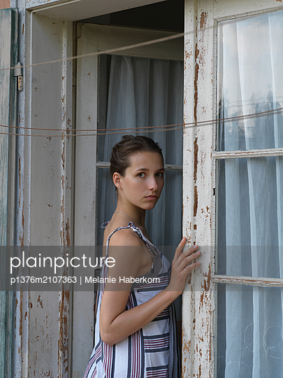 Young woman at open balcony door - p1376m2107363 by Melanie Haberkorn