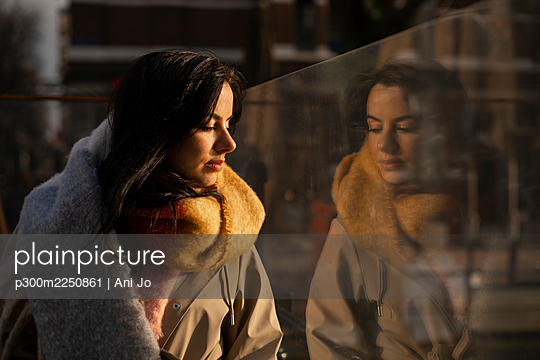 Beautiful woman in warm clothing looking through glass - p300m2250861 by Ani Jo