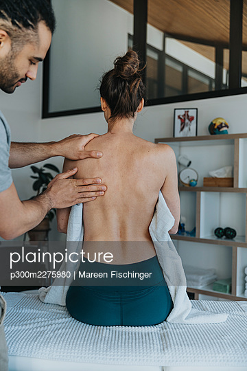 Female patient receiving back and shoulder massage from male physiotherapist in medical practice - p300m2275980 by Mareen Fischinger