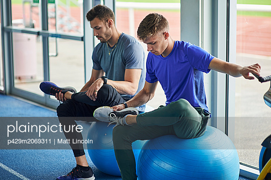 Runners stretching on exercise balls in indoor running track - p429m2069311 by Matt Lincoln