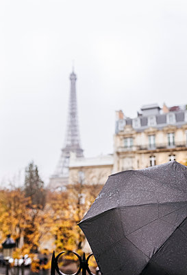 France, Paris, black umbrella with the Eiffel Tower in the background - p300m1416890 by Marco Govel