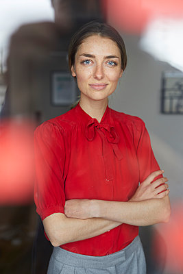 Portrait of smiling woman wearing red blouse standing behind windowpane - p300m1581082 by Philipp Nemenz