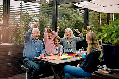 Cheerful family playing board game while sitting at table in backyard - p426m2159828 by Maskot