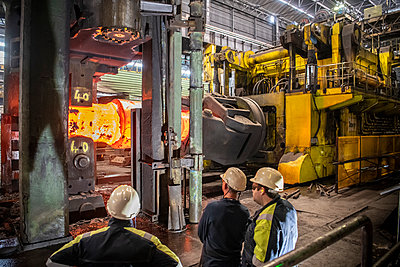 Steelworkers inspecting red hot steel ingot in heavy press in steelworks - p429m2146181 by Monty Rakusen