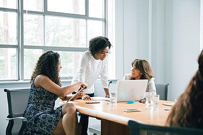 Businesswomen using laptop in meeting - p555m1504109 by John Fedele