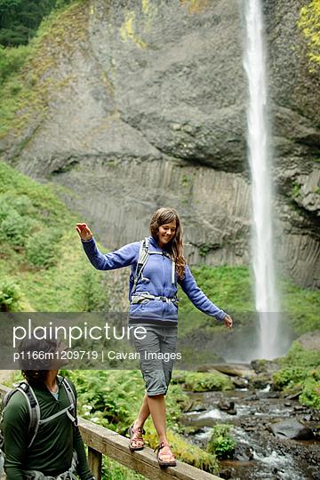 Man looking at girlfriend walking on railing by waterfall - p1166m1209719 by Cavan Images