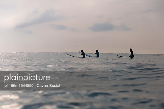 Female friends sitting on surfboards in sea against sky - p1166m1544980 by Cavan Social