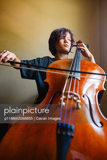 A boy with a serious expression plays cello while looking out window - p1166m2268855 by Cavan Images