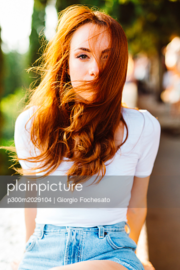 Portrait of redheaded woman with blowing hair - p300m2029104 by Giorgio Fochesato