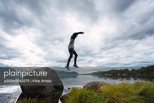 Norway, Senja island, man jumping from a rock at the coast - p300m2042275 von Kike Arnaiz