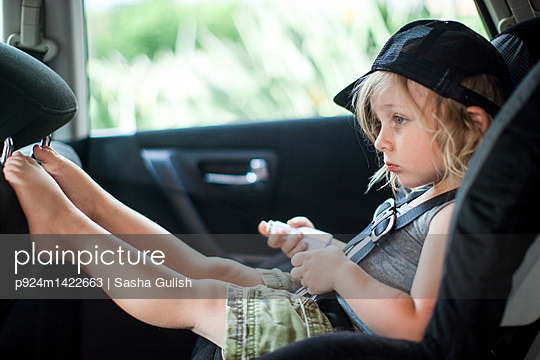 Young boy sitting in child's seat in back seat of car, bored expression - p924m1422663 by Sasha Gulish