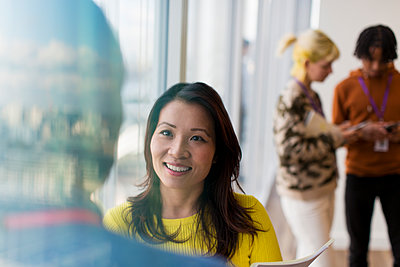 Smiling businesswoman talking with colleague in office - p1023m2212651 by Tom Merton