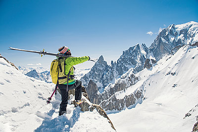 Side view of hiker with skis standing on snow covered mountain against clear blue sky - p1166m1474122 by Cavan Images