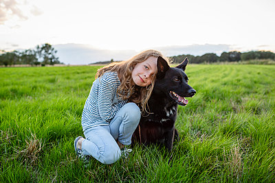 Girl with a dog sitting on a field - p300m2062190 by Julia Otto