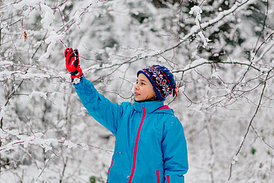Girl standing in a wintry forest - p300m2276075 by Oxana Guryanova