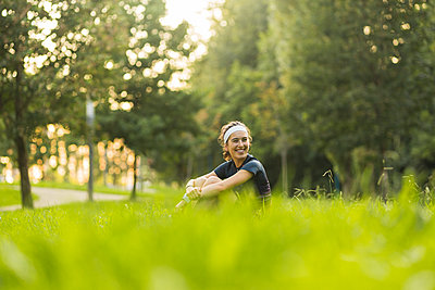 Smiling woman hugging knees while sitting on grass at public park - p300m2282425 by Mikel Taboada