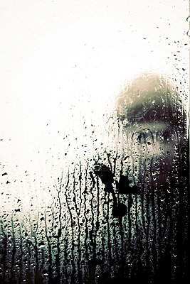 Man looking through rain splattered window - p597m2063522 by Tim Robinson