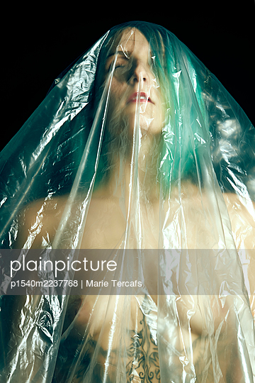 Naked woman wrapped in plastic tarpaulin - p1540m2237768 by Marie Tercafs