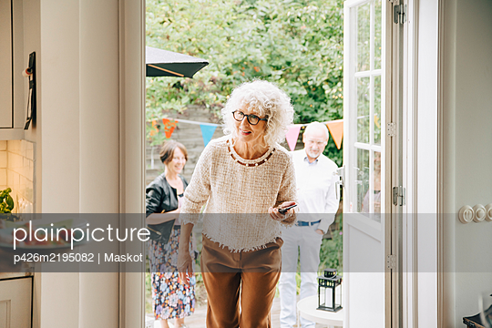 Smiling woman with curly white hair walking through doorway against friends - p426m2195082 by Maskot