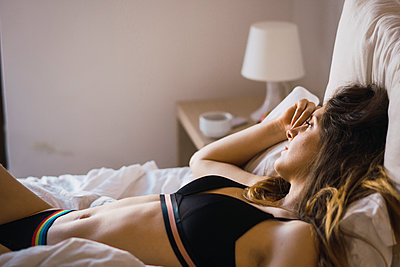 Daydreaming young woman in underwear lying on bed - p300m1581592 by Kike Arnaiz