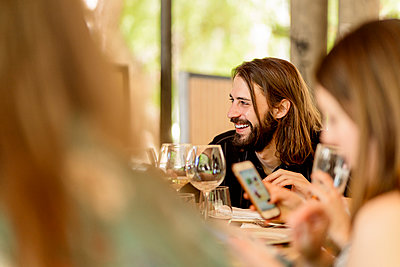 Smiling young bearded man sitting with female friends at restaurant - p300m2202561 by Ezequiel Giménez