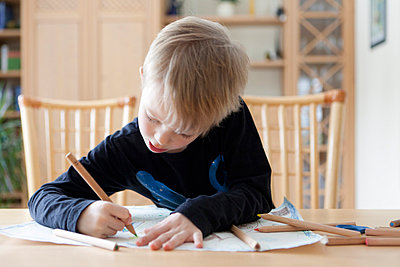 Boy drawing with colored pencils - p42918504f by Stefanie Grewel