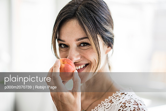 Laughing woman smelling an apricot - p300m2070739 by Robijn Page