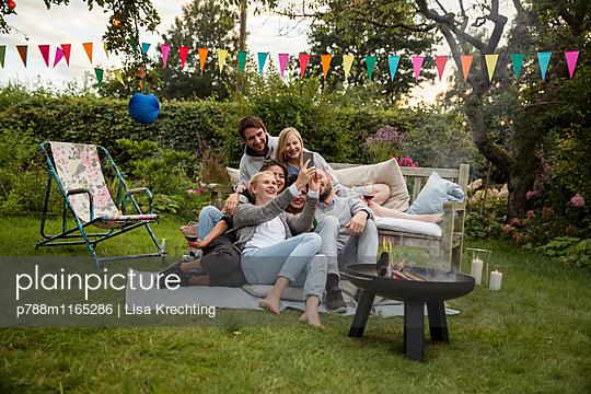Freunde machen ein Selfie auf der Gartenparty - p788m1165286 von Lisa Krechting