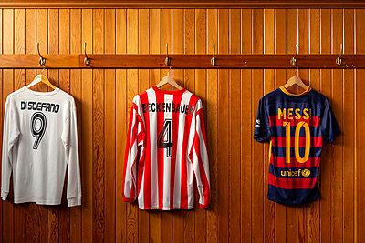 Various football shirts on the coat hook - p1267m2263416 by Jörg Meier
