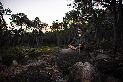 Hiker sits on boulder at twilight - p1640m2261050 by Holly & John