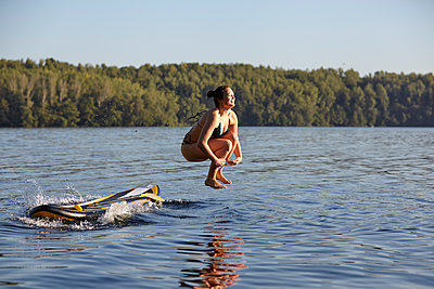 Woman jumping into water from paddleboard - p300m1206222 by Jo Kirchherr