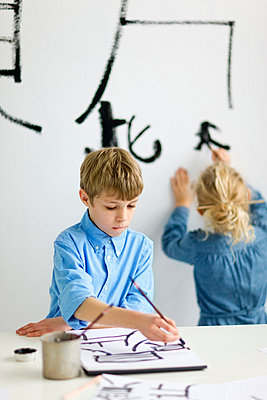 Boy and girl caligraphing chinese signs - p312m670246f by Huett Lundström