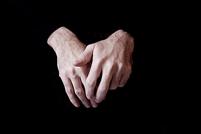Hands of a man with black background - p4450985 by Marie Docher