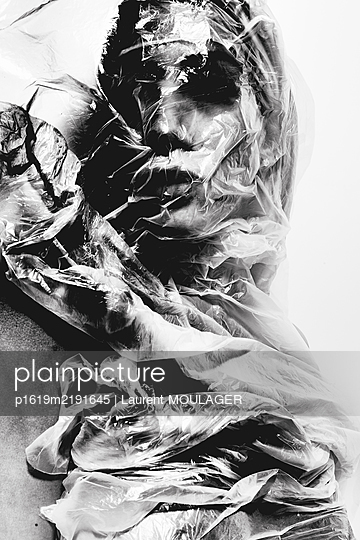 Woman' head wrapped with plastic - p1619m2191645 by Laurent MOULAGER