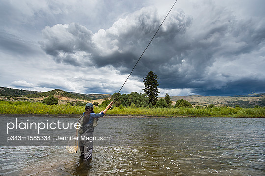plainpicture - plainpicture p343m1585334 - Clouds over women fishing i... - plainpicture/Aurora Photos/Jennifer Magnuson