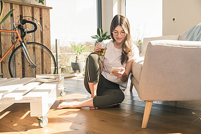 Young woman sitting on the floor at home with drink and cell phone - p300m2103871 by Uwe Umstätter