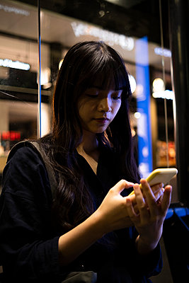 Young woman using mobile phone at night - p300m2290473 by Angel Santana Garcia