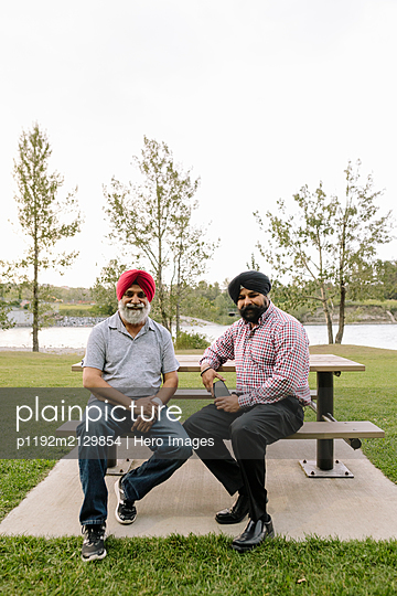 Portrait of mature Indian men on park bench - p1192m2129854 by Hero Images