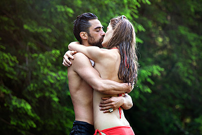 Couple embracing while kissing in forest - p1166m1099434f by Cavan Images