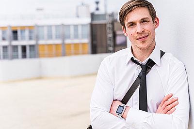 Portrait of smiling businessman wearing smartwatch - p300m1580972 by Uwe Umstätter