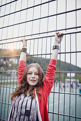 Portrait of a happy teenage girl at a fence at a sports field - p300m2104236 by Roger Richter