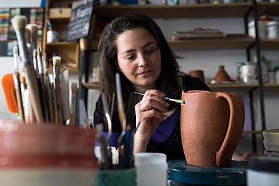 Potter painting unfinished vase in her workshop - p300m2117296 by Andrés Benitez