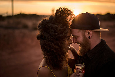 Happy couple with fresh ice tea drink outdoors at sunset - p300m2170627 by Malte Jäger