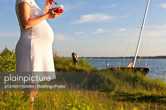 Schwangere Frau isst Erdbeeren am Cospudener See, Leipzig, Sachsen, Deutschland - p1316m1160484 von Roetting+Pollex